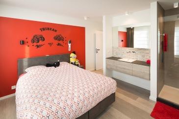 Basiskleur wit met rood als accentkleur schept verbinding tussen kinderkamer en 'master bedroom'
